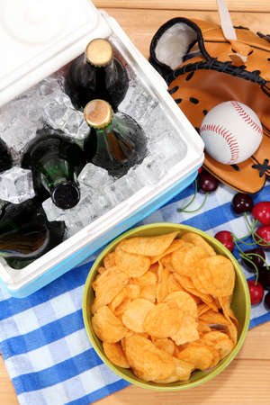 ice chest: Ice chest full of drinks in bottles on color napkin, on wooden