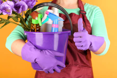 Housewife holding bucket with cleaning equipment on color background. Conceptual photo of spring cleaning. Stock Photo - 27035223