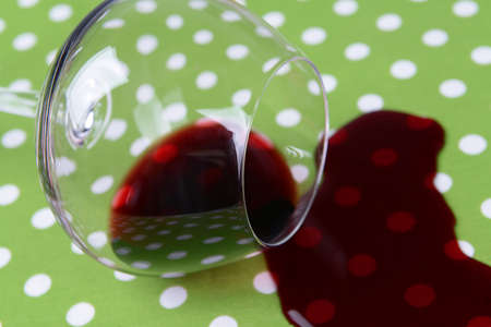 Overturned glass of wine on table close-up photo