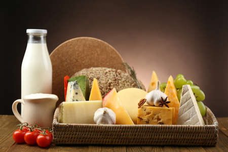 chees: Basket with tasty dairy products on wooden tray, on dark background