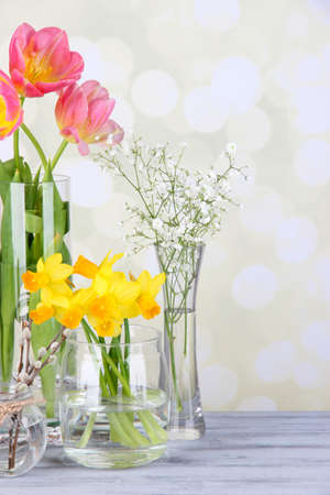 Beautiful spring flowers on old wooden table, on light background photo