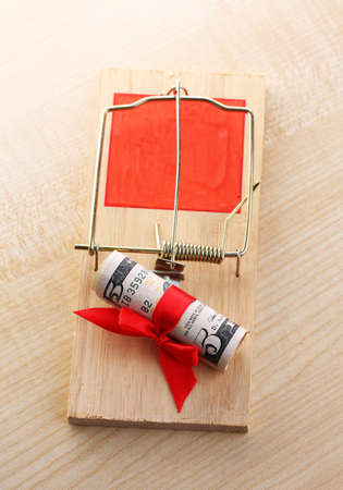 Mousetrap with dollar on wooden background photo