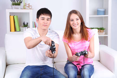 Girl and boy playing video games at home photo