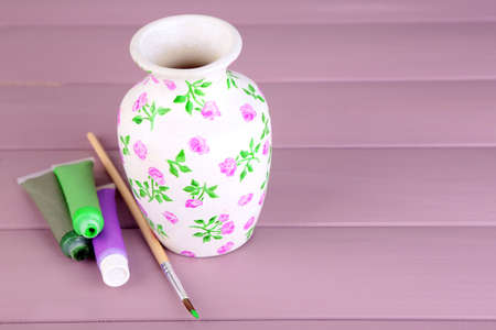 Beautiful hand made vase and art materials on wooden table photo