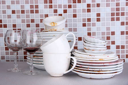 Dirty dishes on bright background