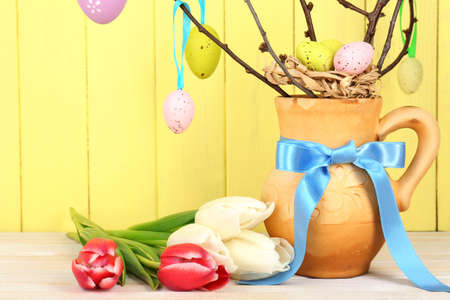 Easter composition with eggs branches on wooden background photo