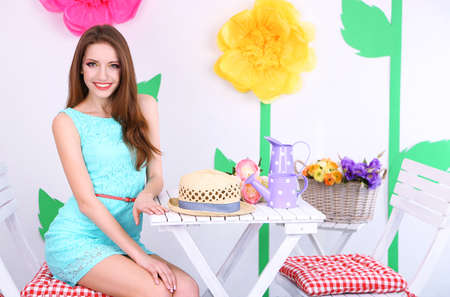 Beautiful young woman sitting on chair at table on decorative  photo