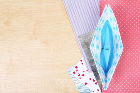 Origami boat and color papers on wooden table photo