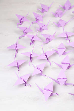 Origami cranes on wooden background photo