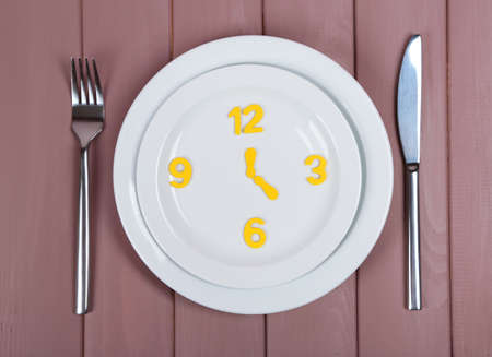microelements: Plate with clock on wooden table close-up Stock Photo
