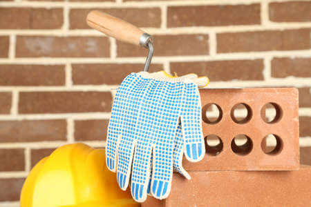 New bricks and building tools on brick wall background photo