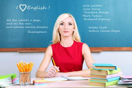Young teacher sitting in school classroom