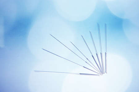 Needles for acupuncture on blue background photo
