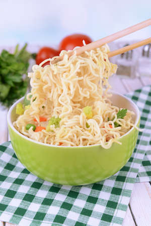 Tasty instant noodles with vegetables in bowl on table on light background photo