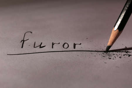 Word Furor and breaking pencil on paper, close up photo