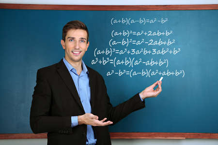 Teacher explaining formulas written on blackboard to  pupils photo
