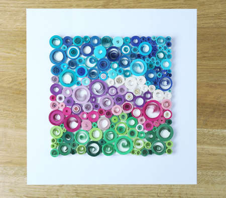 quilled shapes: Abstract colorful picture on wooden background