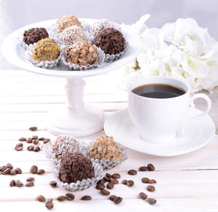Set of chocolate candies on table on light background photo