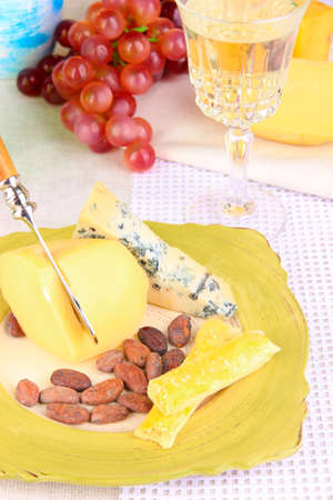 Assorted cheese plate , grape and wine glass on table, on light background photo