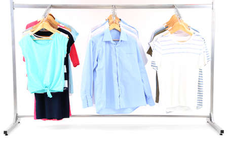 Different clothes on hangers, on gray background photo