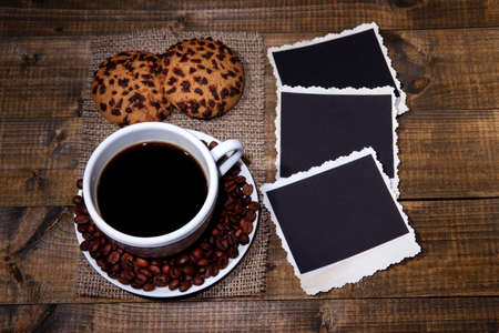 Coffee cup, cookies and old blank photos, on wooden background photo