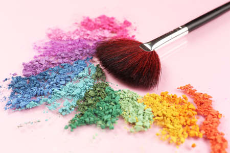 Rainbow crushed eyeshadow and professional make-up brush on pink background Stock Photo