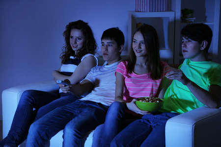 blacking: Group of young friends watching television at home of blacking-out
