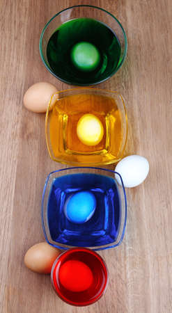 Bowls with paint for Easter eggs and eggs on wooden table photo