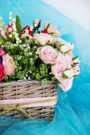 Beautiful flowers in wicker basket, on color fabric and  wooden background photo