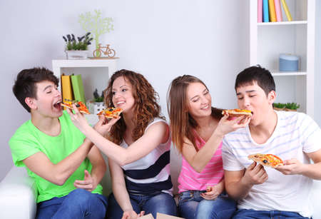 Group of young friends eating pizza in living-room on sofa photo