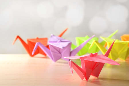 crane origami: Origami cranes on wooden table, on light background Stock Photo
