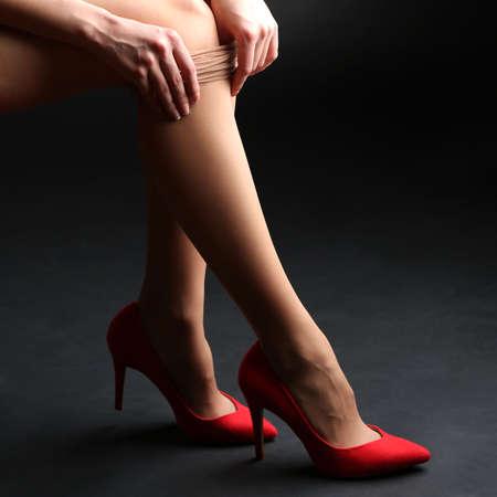 Stockings on perfect woman legs on dark background Stock Photo