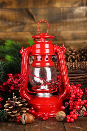 Red kerosene lamp on wooden table on wooden  photo