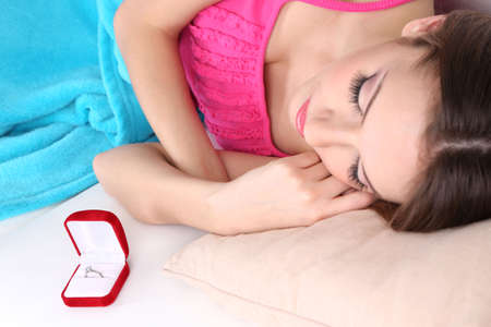 Wedding ring in cute box on sofa near sleeping girl, close-up photo