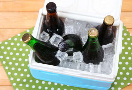 Ice chest full of drinks in bottles on color napkin, on wooden  photo