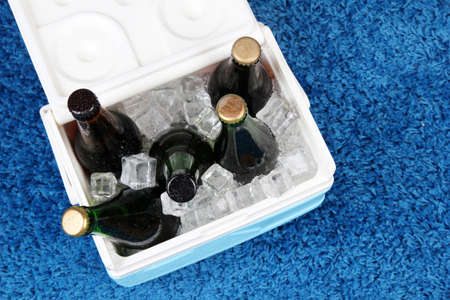 ice chest: Ice chest full of drinks in bottles on color carpet