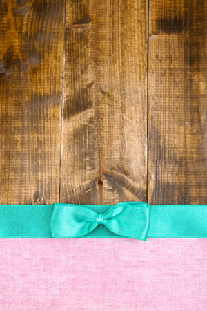 Colorful fabric with color ribbon and bow on wooden background photo