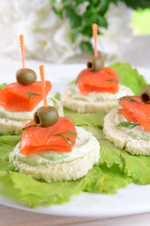 Delicious canapes on table close-up photo