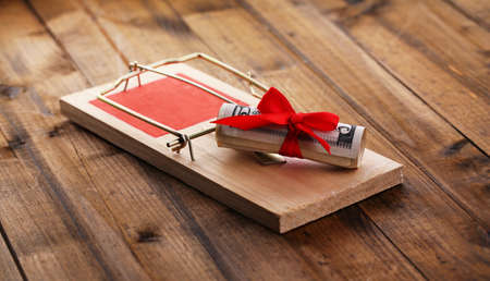 Mousetrap with dollar on wooden  photo