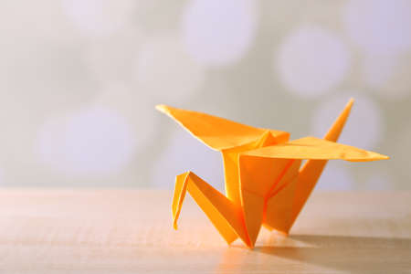 Origami crane on wooden table, on light  photo