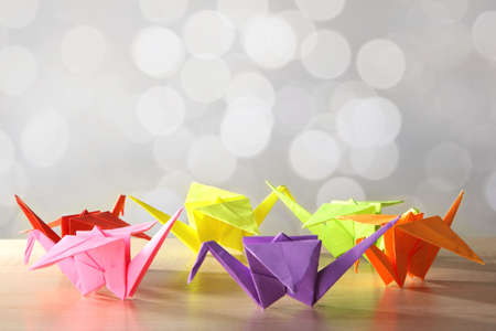 Origami cranes on wooden table, on light  photo