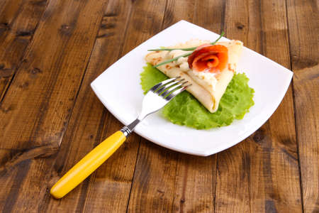 Pancake with salmon, and mayo, green onion, on plate, on wooden  photo
