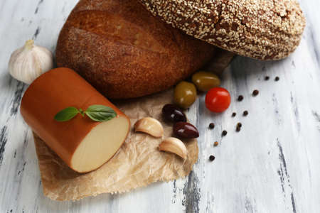 Tasty smoked cheese and bread on wooden table photo