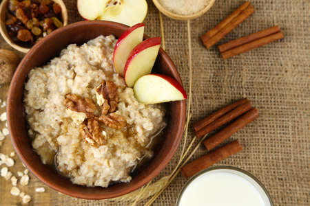 Tasty oatmeal with nuts and apples on table close up photo