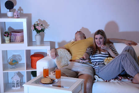 blacking: Young couple watching television at home of blacking-out Stock Photo