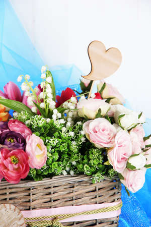 Beautiful flowers in wicker basket, on color fabric and  wooden  photo