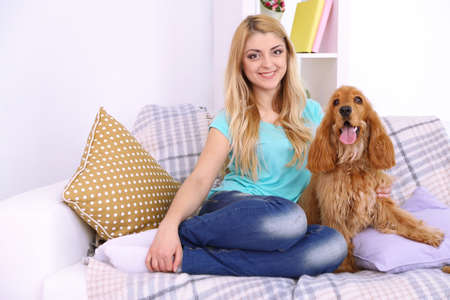 Beautiful young woman with spaniel on couch in room photo