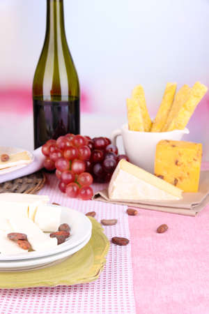 Assorted cheese plate , grape and wine glass on table, on light  photo
