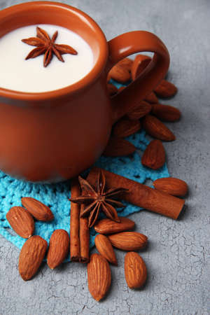 Almond milk in jug with almonds in bowl, on color wooden background photo