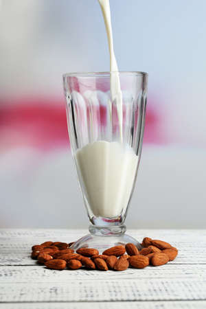 Almond milk is poured into glass, on color wooden table, on light  photo